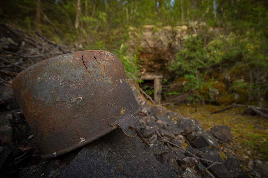 An old bucket sits at the entrance of an abandoned mine located along the shores of Tazin Lake in Northern Saskatchewan