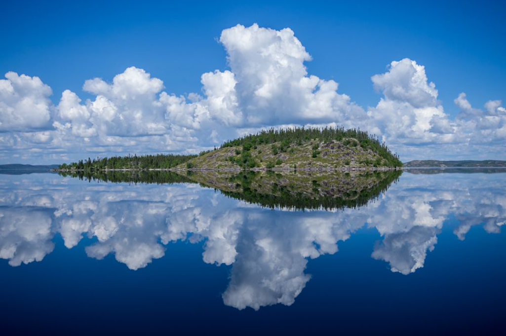 A perfect reflection of an island on a sunny morning on Tazin Lake, Saskatchewan