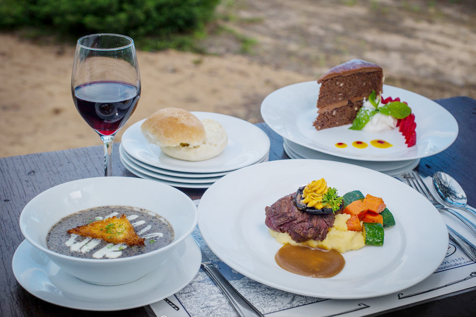 A lovingly crafted gourmet meal consisting of soup, steak, potatoes, steamed vegetables and cake for dessert, a part of a guest's experience at Tazin Lake Lodge, Saskatchewan