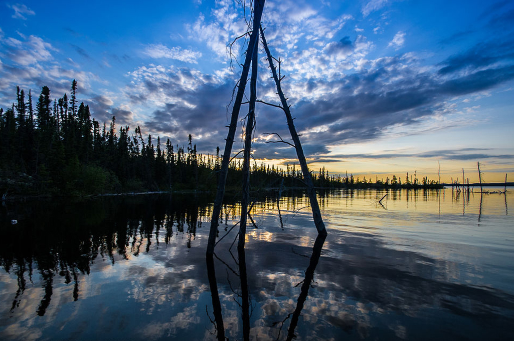 The sun sets on a beautiful evening in Tazin Lake, Saskatchewan.  A structure constructed with three logs resembles a tipi sits in the water.